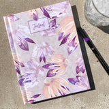 Journal with pink, tan, and salmon floral pattern watercolor on table