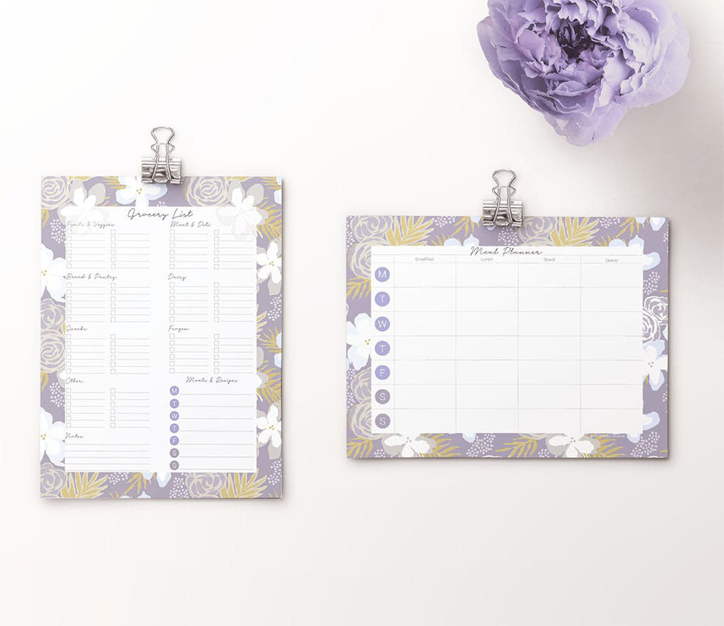 Downloadable grocery list and meal planner pages shown on binder clips with purple flower in corner. Pattern around pages is gray blue with white, blue, yellow.