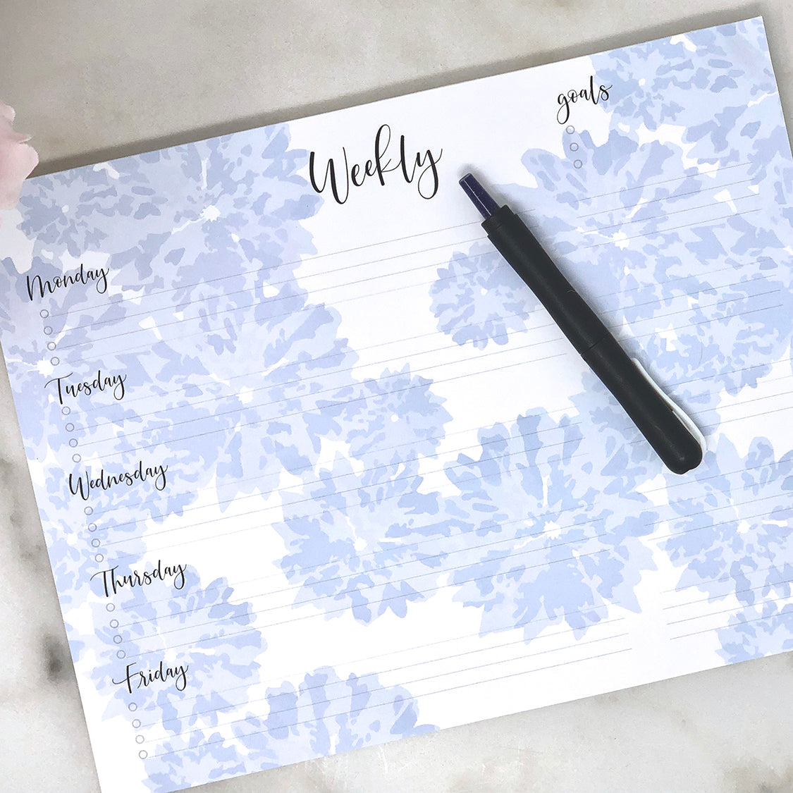 Weekly notepad blue on white with black type in use