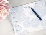 Weekly notepad blue on white with black type on desk