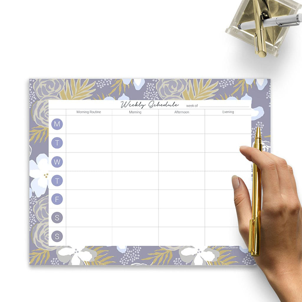 Weekly Planning Pad with floral botanical border pattern on a white surface. Woman's hand holding gold pen, pencil cup in upper right corner