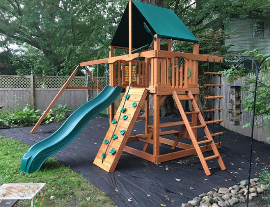 gorilla chateau swing set with classic green vinyl canopy in backyard