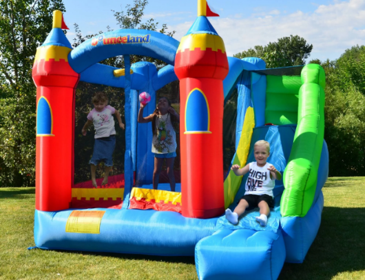 kids bouncing on the bounceland royal palace bounce house with slide