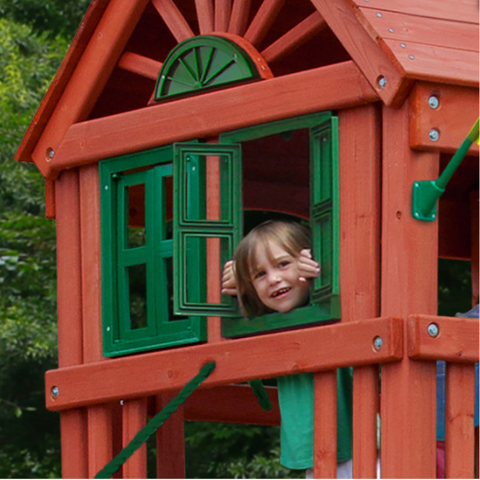 Girl looking out real working shutters on gorilla playset