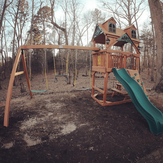 chateau swing set with malibu wood roof in the yard