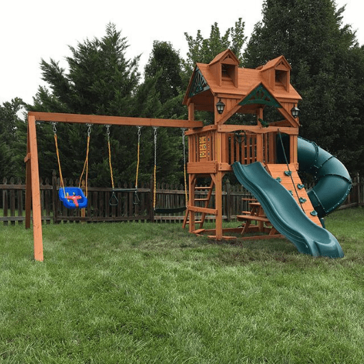 mountaineer swing set with treehouse rood in the backyard