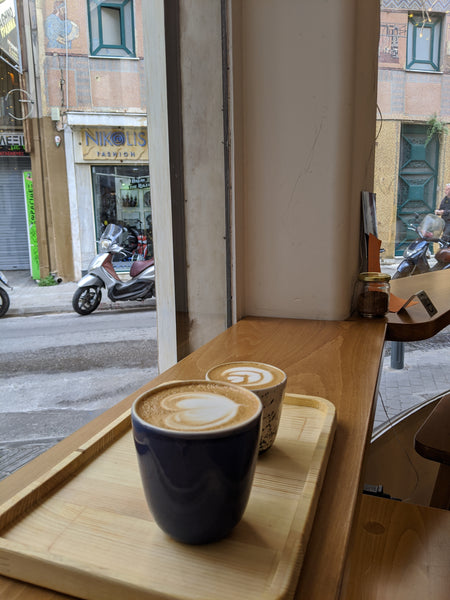 Two coffees on a bar at a window