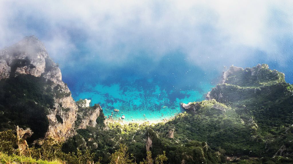 Image of Mediterranean Sea from birds eye view. There are rocks and a small beach