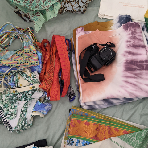 Swimsuits and a tie dye sweatshirt folded on a bed with a camera
