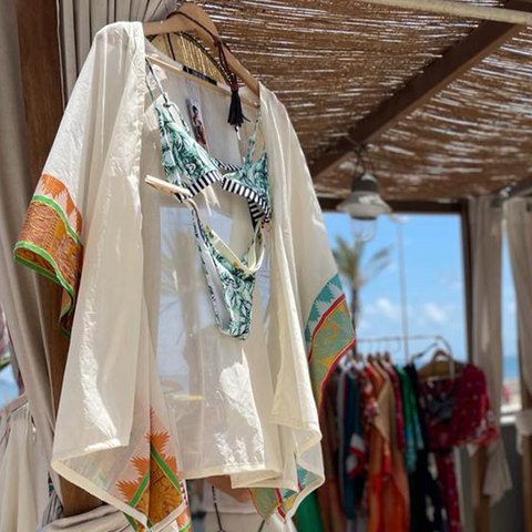 A white jacket on a hanger with a floral and striped bikini underneath