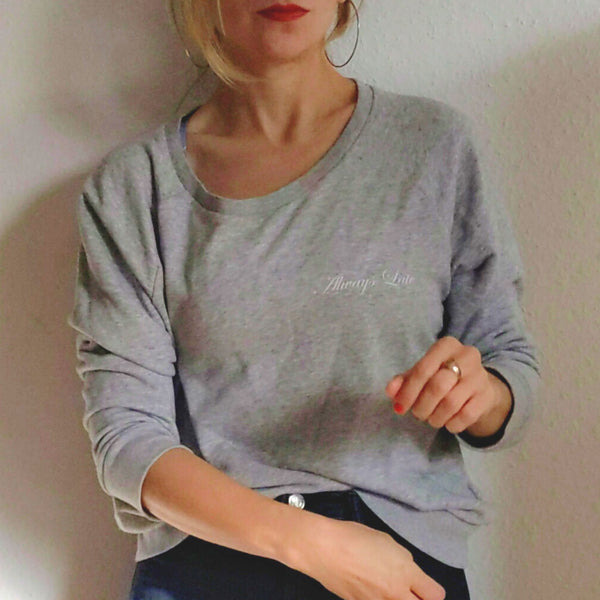 "Light grey wide neck dolman sleeve sweatshirt with ""Always Late"" in cursive font"