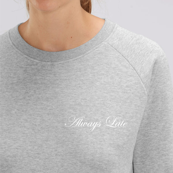 "Close up of Light grey wide neck dolman sleeve sweatshirt with ""Always Late"" in cursive font written"