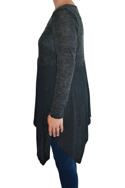 Side view of asymmetrical hem knit top with long sleeves.