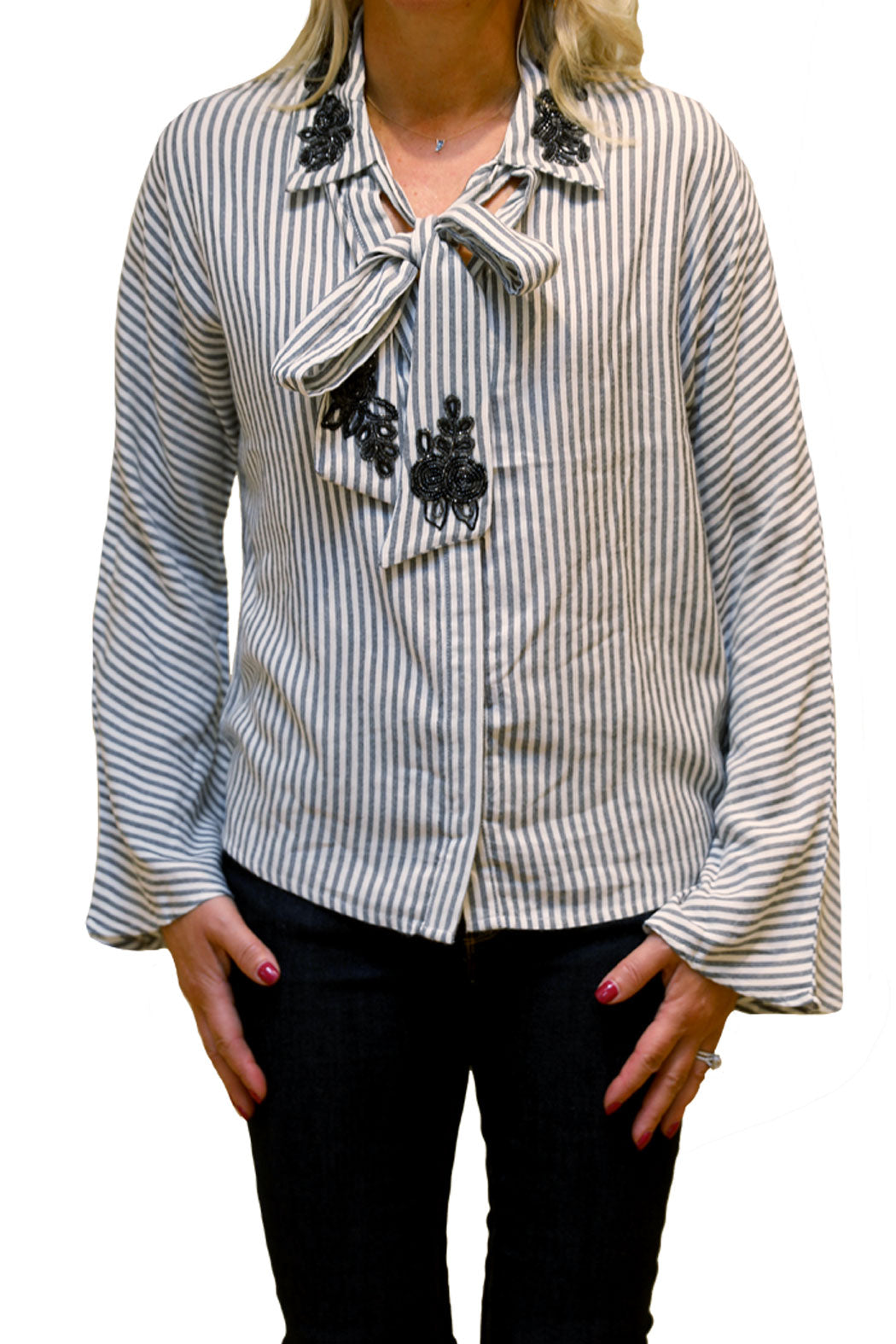 Front view of striped long sleeve blouse with embroidered detailed at collar and neck tie.