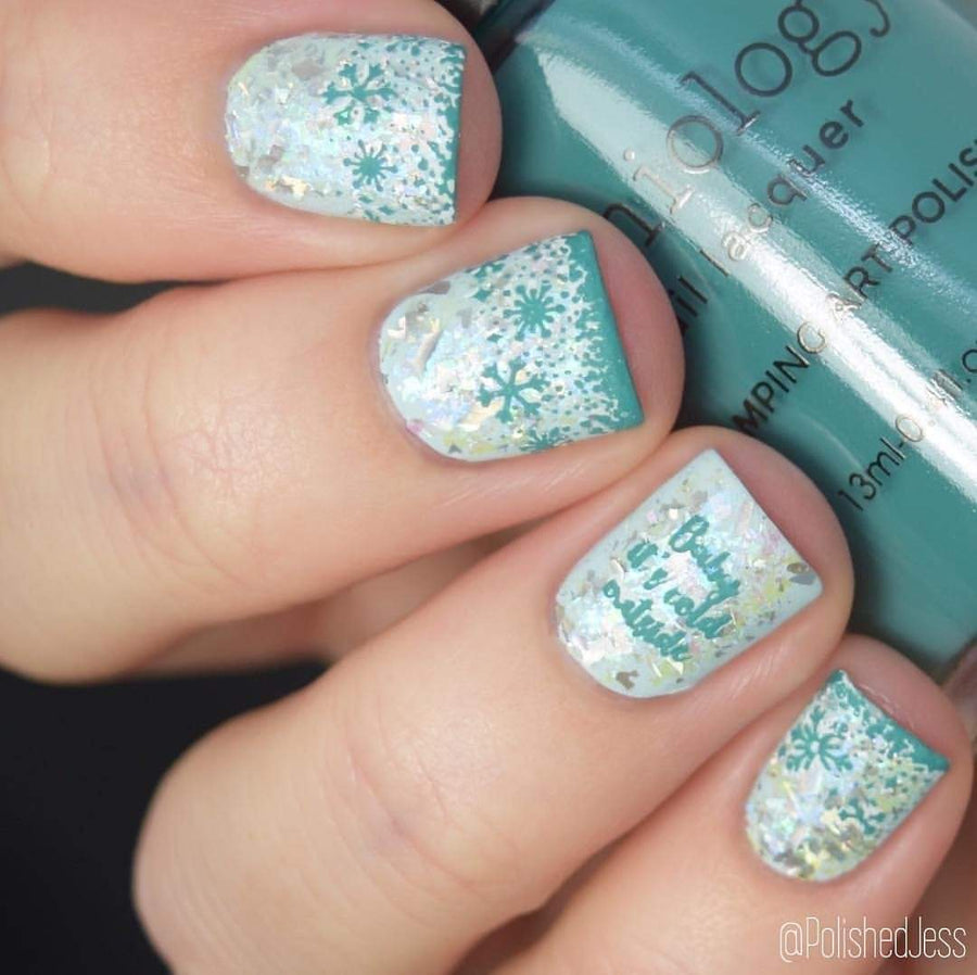 A manicured hand holding an Icy Blue Stamping Polish by Maniology