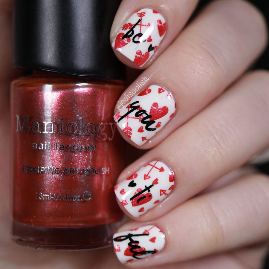 A manicured hand holding Galentine (B329) Metallic Red Stamping Polish by Maniology.