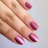 A manicured hand with Razzle Dazzle (NA017) Pink Holographic Nail Art Powder.