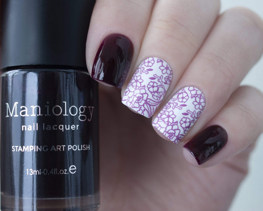 A manicured hand holding sheer purple tinted stamping polish Violet Spectrum (B274) by Maniology.