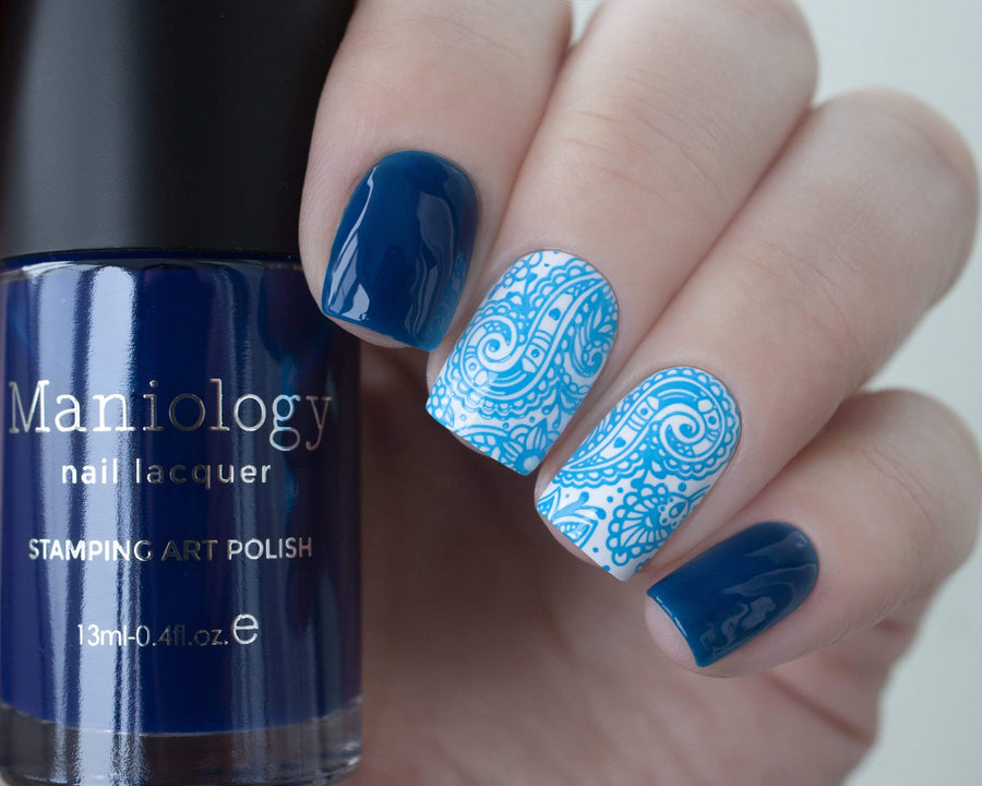 A manicured hand holding Sheer Blue Stamping Polish from Rainbow Splash Collection Ocean Depth (B276) by Maniology.