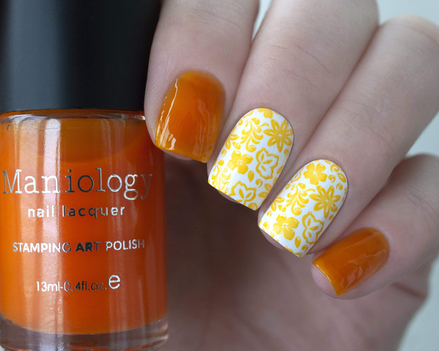 A manicured hand holding Sheer Yellow Stamping Polish from Rainbow Splash Collection: Sunny Day (B271) by Maniology.