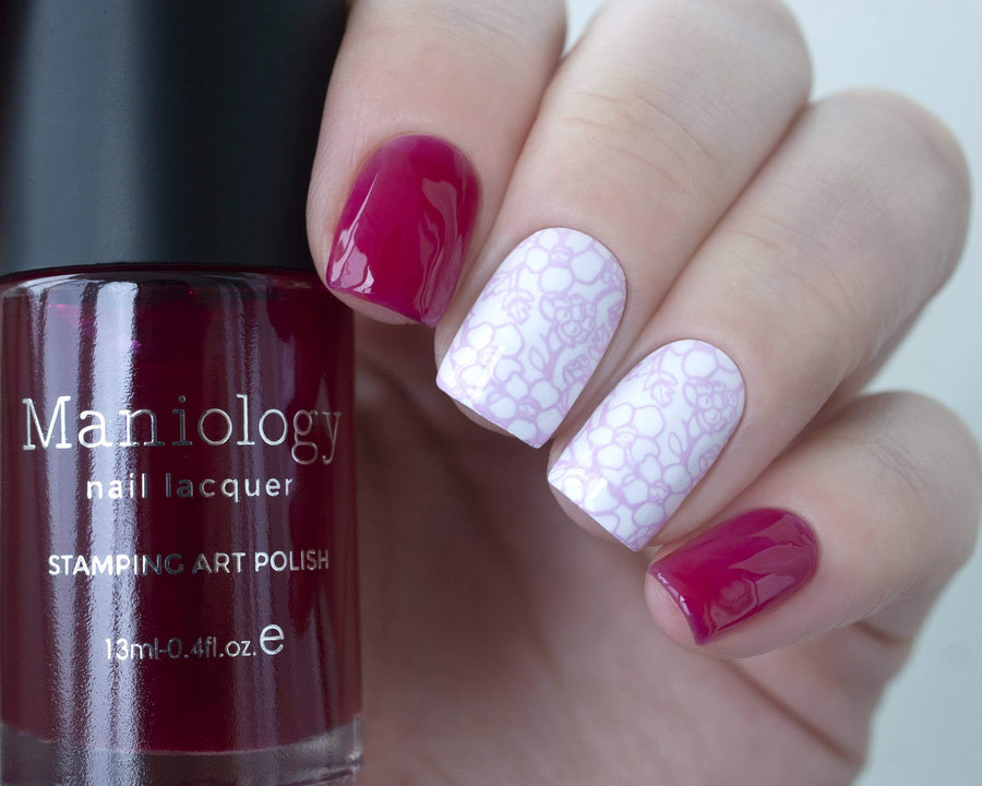A manicured hand holding Sheer Magenta Stamping Polish from Rainbow Splash Collection: Vermillion (B273) by Maniology