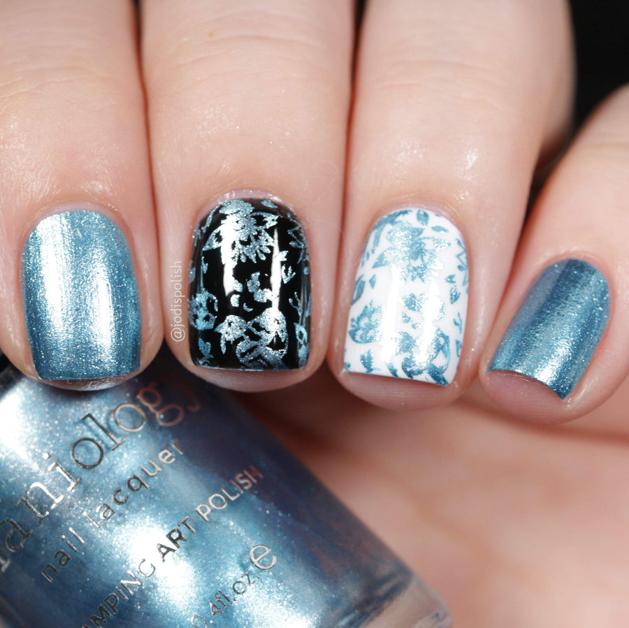 A manicured hand holding metallic blue stamping polish from Soiree All Day collection Bubbly (B322).