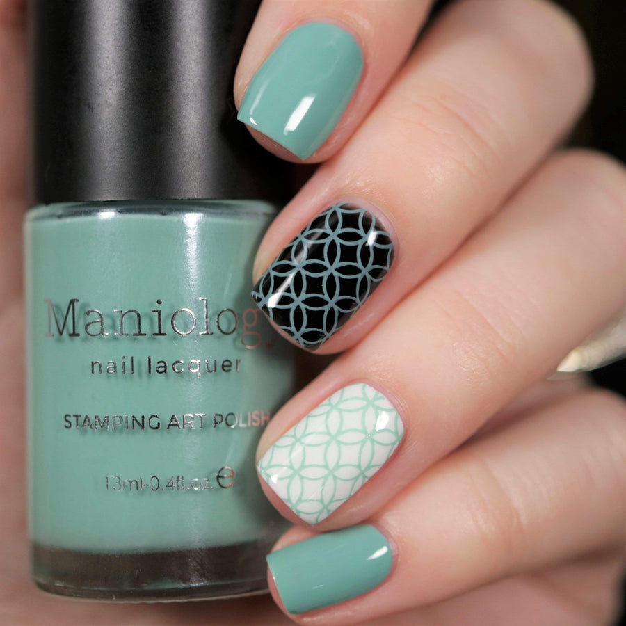 A manicured hand holding Dusty Blue Stamping Polish from Stocking Stuffer collection Morning Snow (B312).