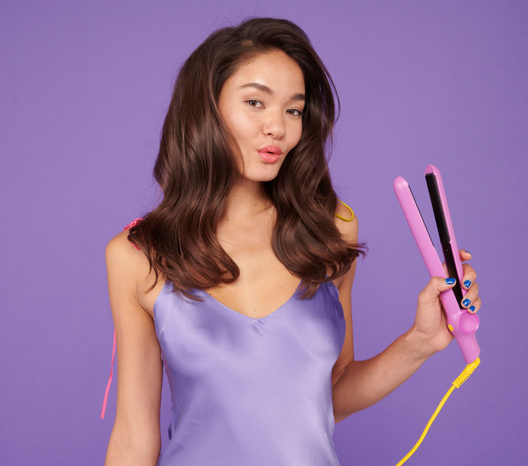Woman straightening her hair with the Flower Ceramic Styling Iron