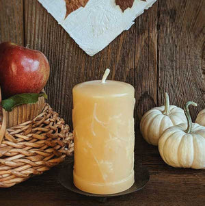 Beeswax pillar candle with maple leaves design.