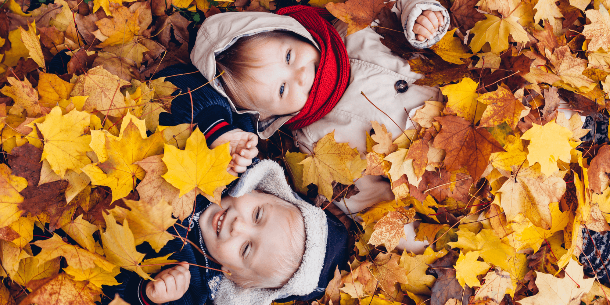 Little boy and girl playing outside in the leaves