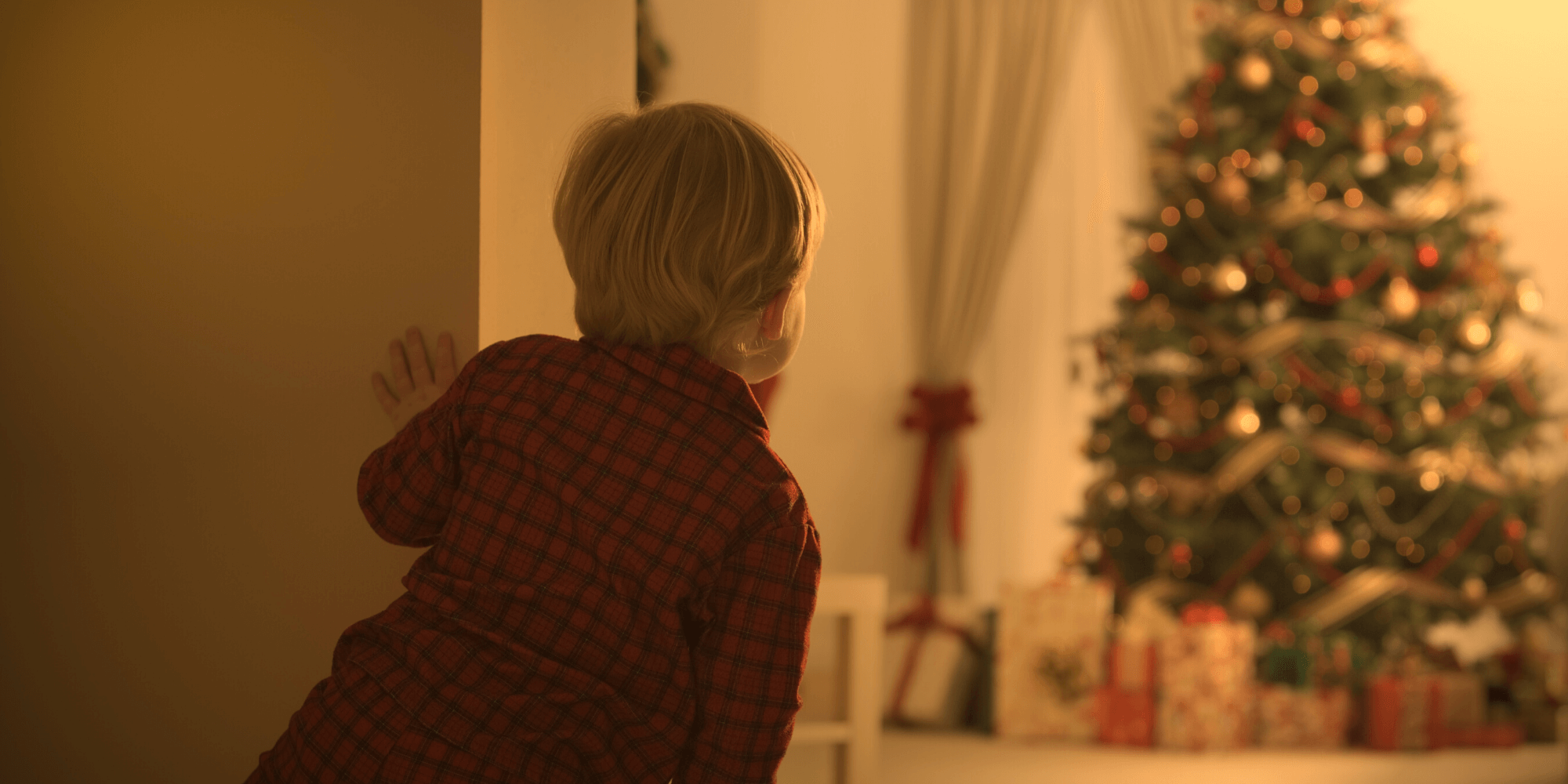 Little boy looking at Christmas tree and presents
