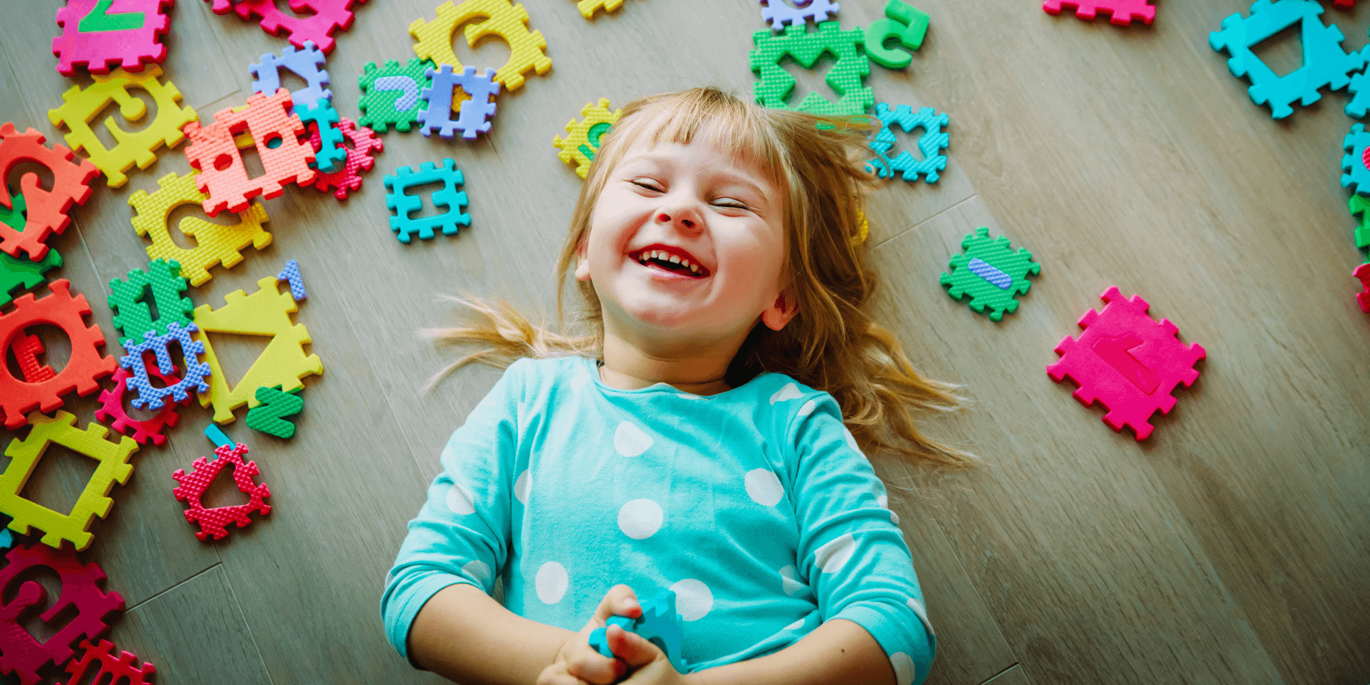Little girl laughing playing with letter block toys