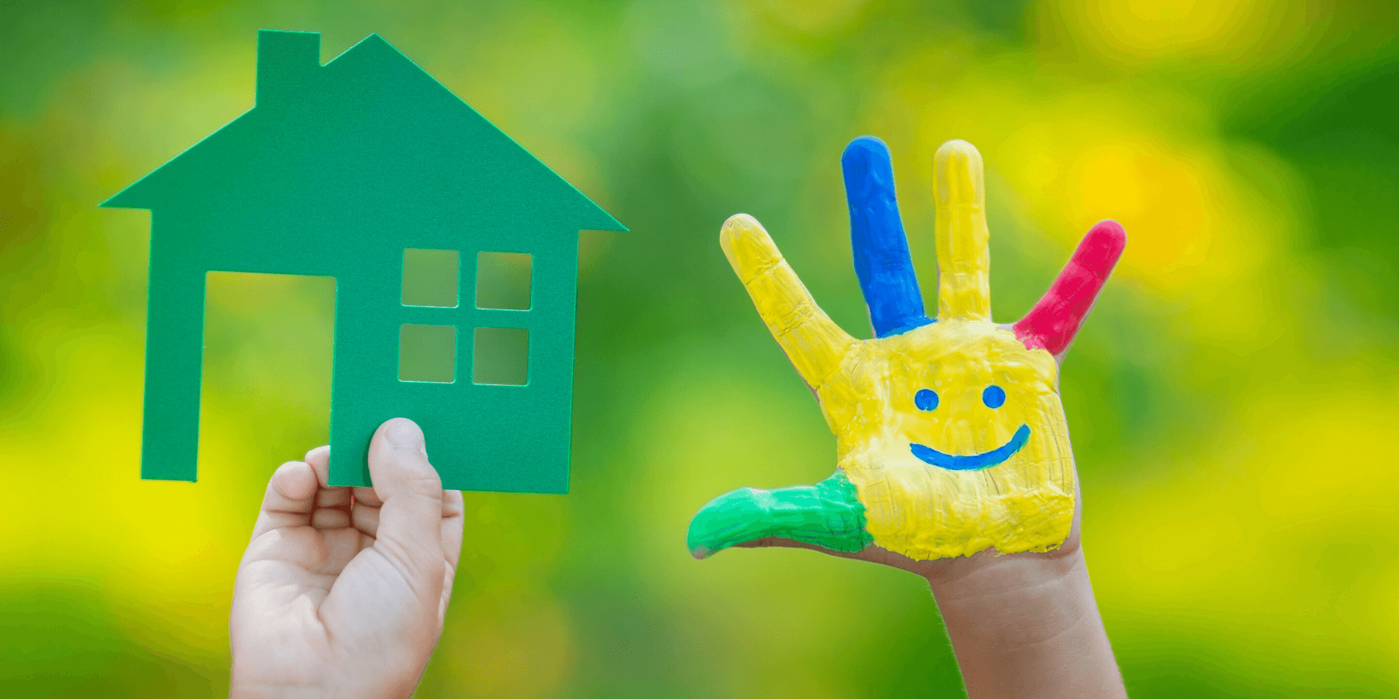 Little child holding a paper cutout house and a painted hand