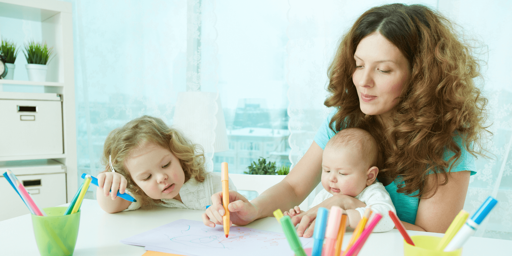 Mother drawing at home with her baby son and daughter