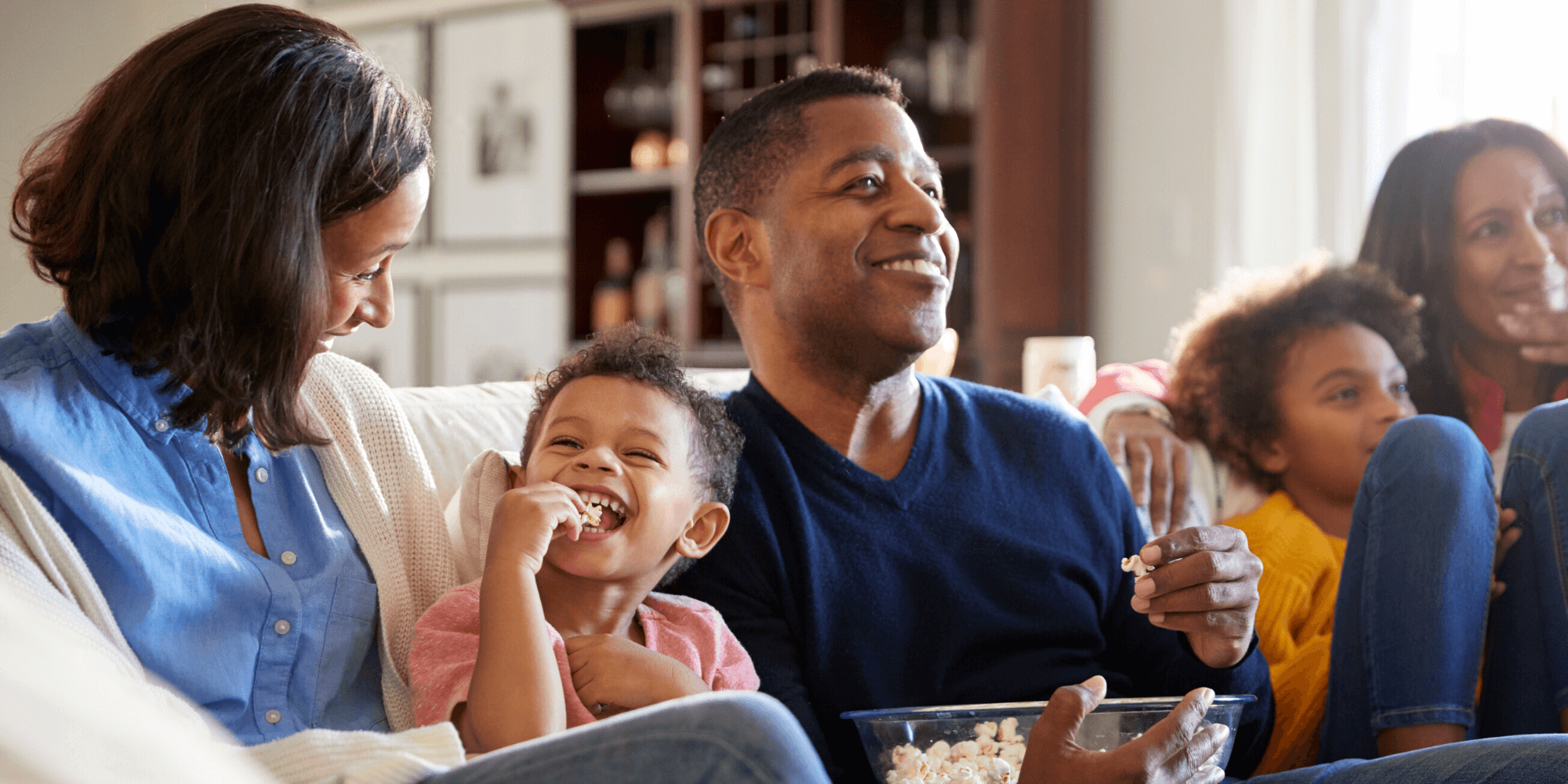 Family watching movies at home with popcorn