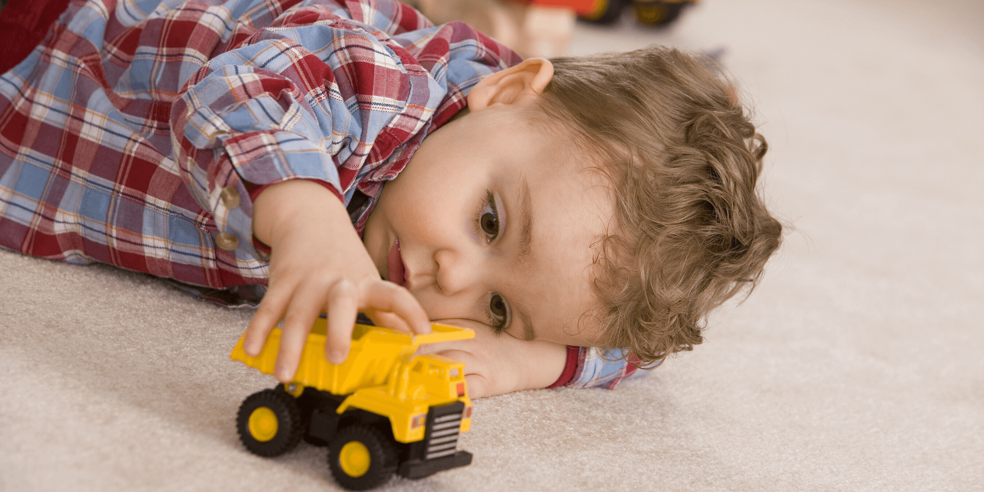 Little boy playing with his yellow toy car