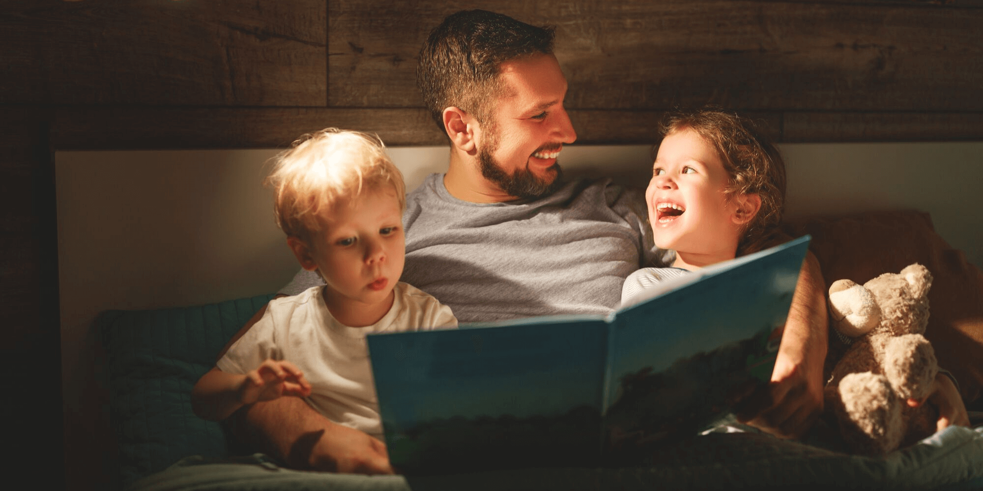 Father reading a bed time story to his children