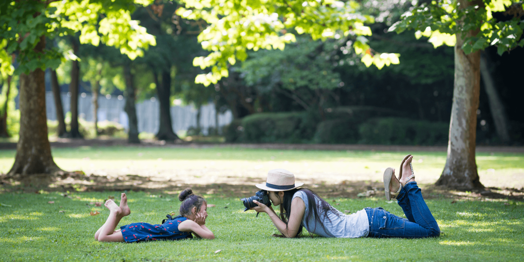 Mother taking picture of her daughter in the park