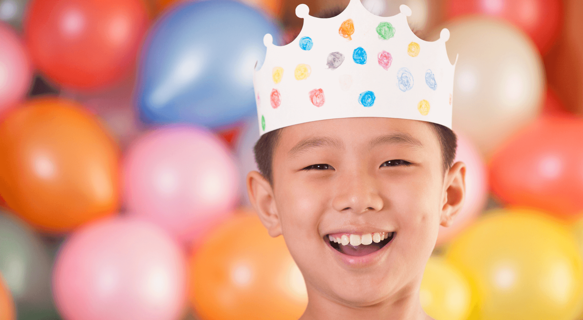 child with party hat and smiling