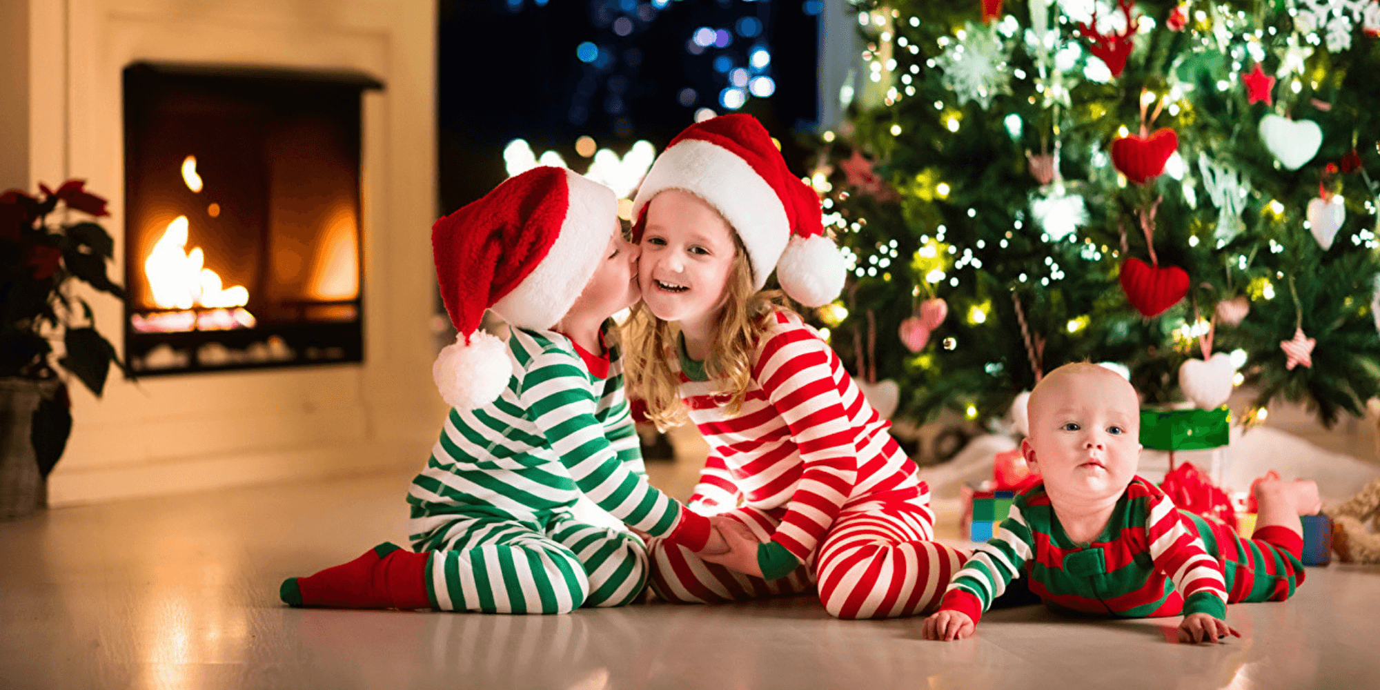 children sitting by the Christmas tree