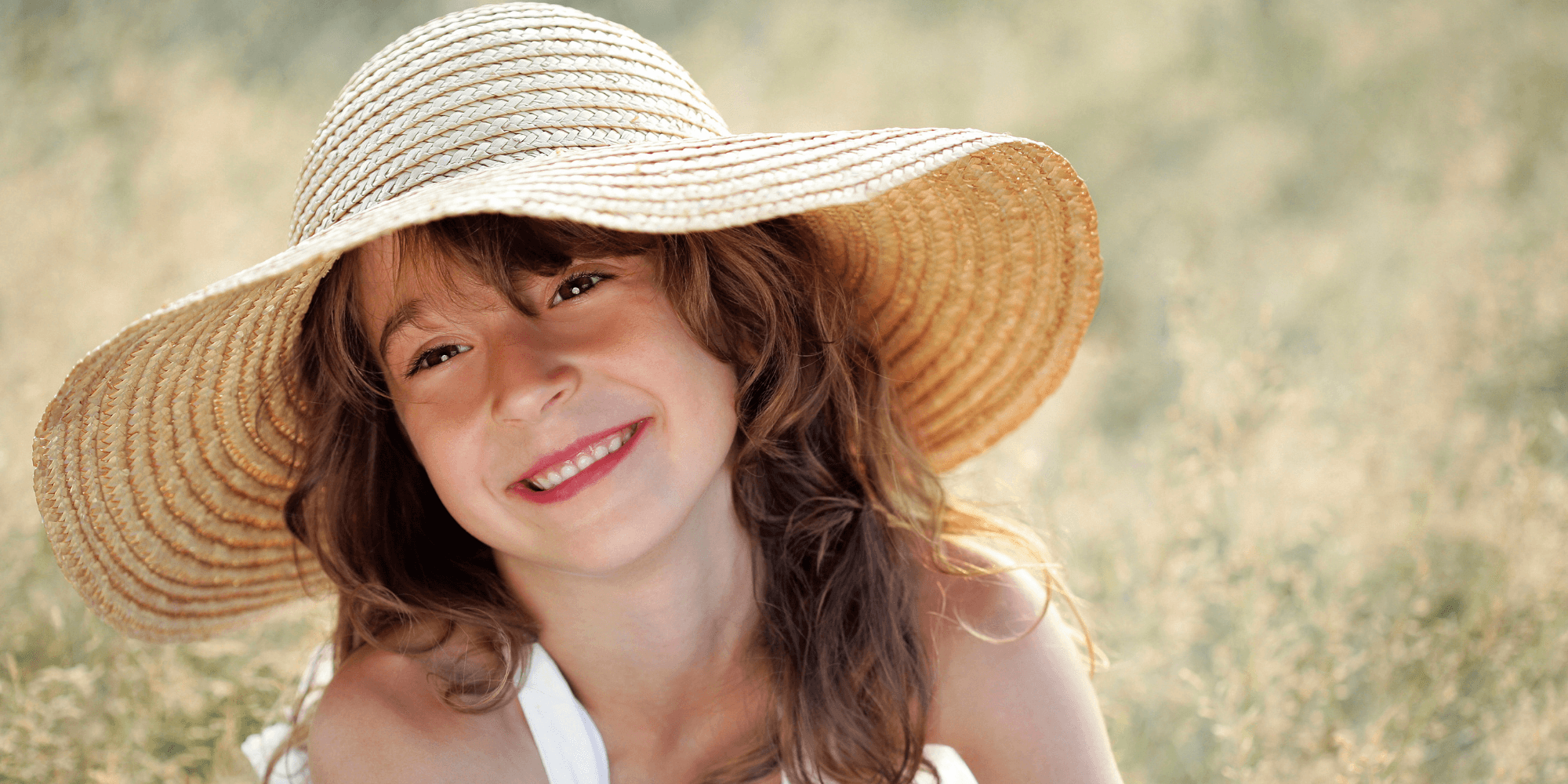 Little girl in a sun hat smiling