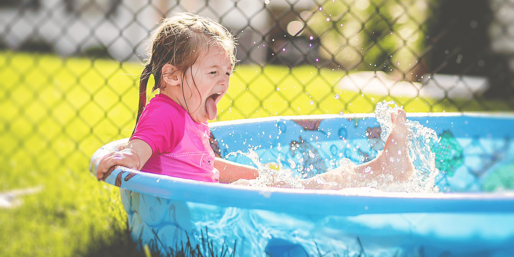 Little girl having fun in a paddling pool