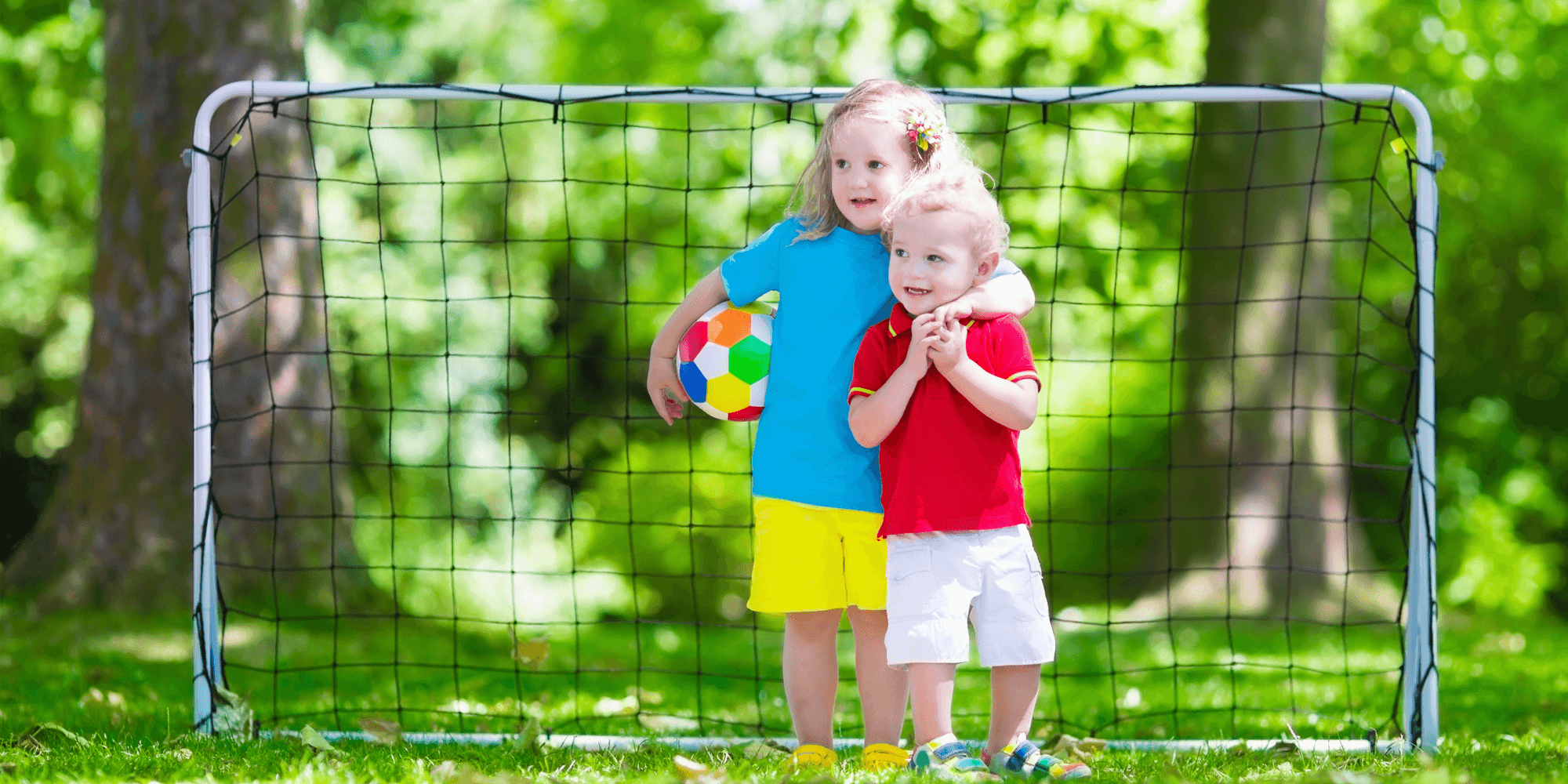 Siblings playing with football