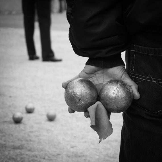 Black and white image of hand holding bowls balls