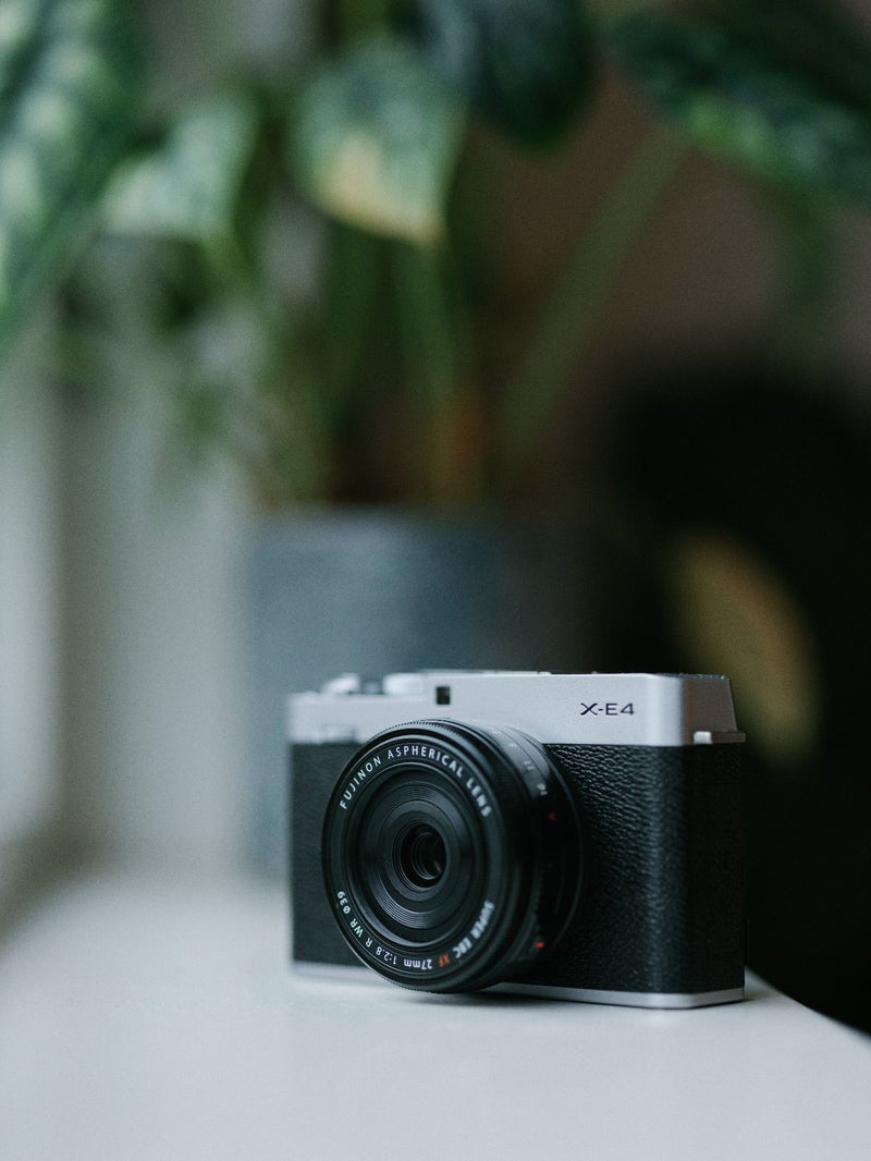 Fujifilm X-E4 Camera in black and silver with lens on window sill