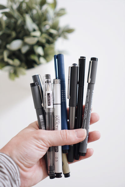 Best Pens + Adhesives for Journaling, adhesive dots, pens in hand