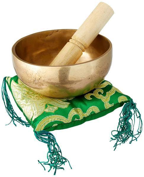 plain singing bowl with mallet inside placed on a green square pillow with tassles