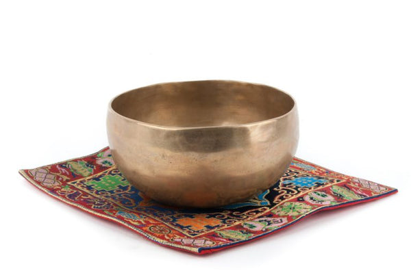 plain singing bowl placed on a red mat with colorful embroidery
