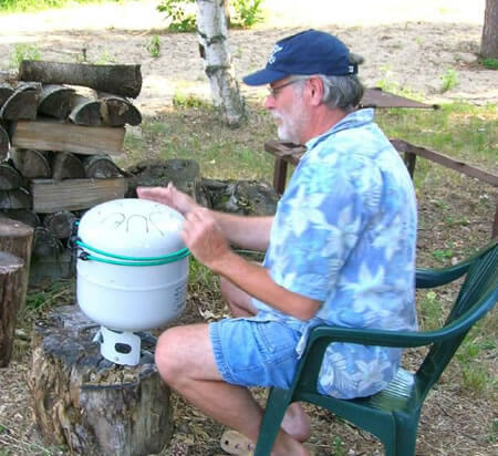 old man wearing blue button down shirt and shorts playing white medium sized steel drum