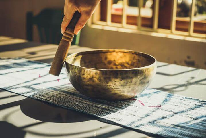hand holding wooden mallet circling rim of a medium sized singing bowl
